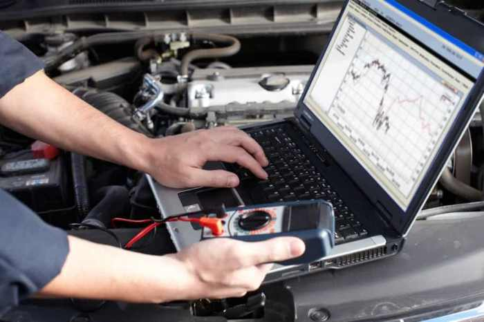 Auto mechanic inspecting engine computer to determine if PCMS needs to be repaired or replaced.